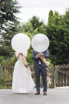 Wedding Photography Idea: Hold giant balloons with tassels for fun couple portrait.