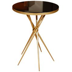 Brass and Black Glass Hollywood Regency Side Table 1940s A beautiful Art Deco design, this brass side table is petite and sophisticated, fitting in between a pair of side chairs perfectly or alongside a single reading chair. Truly elegant, the criss-crossing of the base, banded together in the center, allows for minimal use of floor space and lends a provocative profile to the piece. Rare and gorgeous!