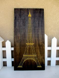 This is a custom order I made for a friend. This is a sign I made by hand-cutting and staining wood. The wood is a dark brown stain and the eiffel
