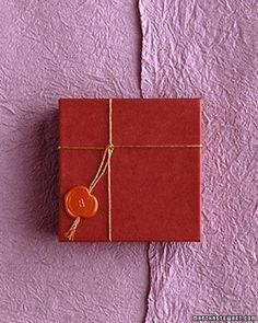A copper-cord tie is finished with a monogrammed wax seal.