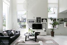 Modernia mustavalkoista tyyliä olohuoneessa, joka täyttyy suurista ikkunoista tulvivasta valosta