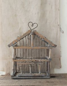"a shabby little bird cage. we love the bits of pale blue paint and natural bird ""patina."" hangs from a heart shaped hook."