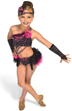 Jazz/Musical Theatre Costume:  Gorgeous Award Winning Custom Costume.  This costume features a hot pink lycra one shoulder top with black lace and black/pink tulle embellishments.  It has 2 shoulder straps and 3 straps from the top to the waist.  The bottoms are both hot pink and black lycra with a black lace overlay.  The beautiful layered bustle with floral embellishments is made of 4 different black and hot pink tulles and mesh.  The details on this costume are incredible!  T...