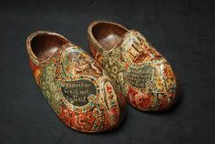 A pair of painted century Hindelooper clogs painted with flowers and biblical scenes.
