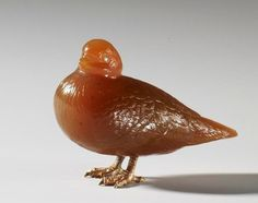Pouter pigeon fabergé  A brown agate pouter pigeon with rose cut diamond eyes and chased gold legs.   Provenance  Commissioned by King Edward VII, 1907 (the Sandringham Commission)
