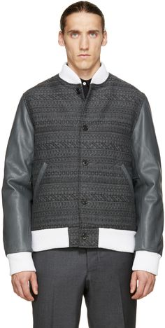 Long sleeve bomber jacket in tones of grey. Ribbed knit stand collar, cuffs, and hem in white. Button closure and leather-trimmed welt pockets at front. Leather paneling at sleeves. Textured weave throughout body. Quilted lining. Welt pockets at interior. Tonal stitching.