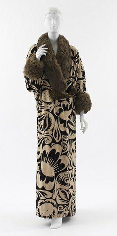 1911, designed by Paul Poiret. Fur trims with flower printed, long columnar dress  Chiếc váy dài này mang phong cách quý tộc, sang trọng và quý phái
