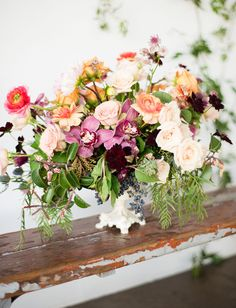 Wild spring centerpiece with orchids, ranunculus + roses