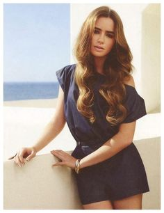 Soft Wave, Light Brown Hair, Navy Blue Short Sleeve Romper, Gold Bangle Bracelet, Full Eyebrows; Lily Collins.