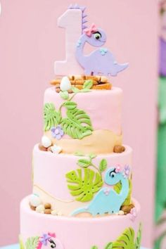 Don't miss the amazing pink tiered birthday cake decorated with pretty fondant girly dinosaurs at this pretty girl dino birthday party! See more party ideas and share yours at CatchMyParty.com #catchmyparty #partyideas #4favoritepartiesoftheweek #dinosaurs #girldinoparty #dinsoaurparty #dinosaurcake