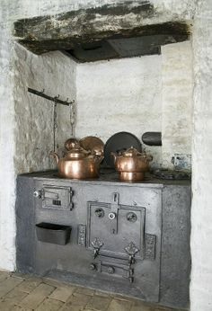 Cast Iron Stove  and  Copper Pots Now that is an old stove in its original kitchen I bet!