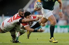 Michael Leitch and Fumiaki Tanaka of Japan try to stop Handre Pollard
