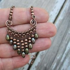 This necklace combines the great patina of antiqued copper with wire wrapping and freshwater pearls. Rows of copper beads and freshwater pearls by marlene