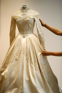 """Elizabeth's wedding gown as it appeared  in preparation for auction by Christie's in 2013, where it fetched $188,000. The gown was made of 25 yards of ivory silk satin, with """"illusion"""" lace shoulders and all-over embroidered decorations of bugle beads and seed pearls."""