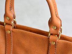 ファスナー付きの2wayトートバッグ。使う人や場面を選ばないシンプルなデザインが魅力のファスナー付きの2wayトートバッグ。仕事でも普段でも使えるバッグなので、始めて革鞄を使う方にもお勧め出来ます。