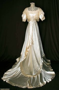 SILK SATIN & LACE WEDDING GOWN, 1912-1914. Brussels lace & Pt. de Gaz h.m. lace bodice, trained cream silk skirt, draped side panels, wide self fabric waist sash, low CF knotted silk fringe w/ double garland of strung silk looped balls. American labeled Petersham. Back