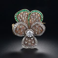 Art Nouveau pansy pin featuring shimmering Plique-a-Jour (translucent) enamel petals which effectively emulates the look of frosted crystal. Superb calibre emeralds and twinkling rose-cut diamonds outline the five petals and tiny rose-cuts also dot the platinum lattice work inside. A .55 carat European-cut diamond beams from the center of the this fabulous bejeweled flower, finely crafted in platinum over gold, circa 1900.