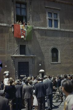 Allied troops on the flag draped balcony of Palazza Venezia, from which Mussolini used to address the people of Rome, while people celebrate below them