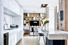 House tour: a designer's London home of epic proportions: In the kitchen, customised shelves to display CLARICE CLIFF vases; Kelly Hoppen chairs; stools from French Connection Home; on wall, Serge Mouille lamp.