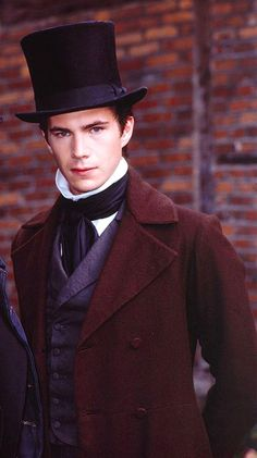 """In his long, ruffled chemise, riding breeches & black boots, James D'Arcy looks every inch the dashing Victorian hero. The aquiline features, dark, saturnine eyebrows & hair styled in the champion's quiff all add to the effect. Instead, during a break from filming Nickleby, he folds his 6ft 3in frame into a very out of period plastic garden chair, clutches an equally futuristic polystyrene cup of tea & idly wonders whether to have a thoroughly modern McDonald's for his lunch."""