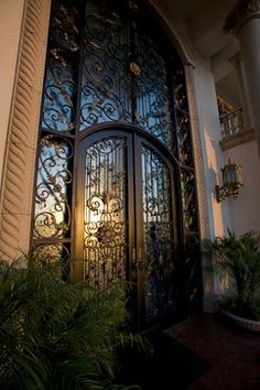 Ornate wrought iron and carved stone Mediterranean front entrance | Sweany Custom Homes ᘡղbᘠ