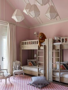 "To create a lively, fun vibe in the oldest daughter's room, Hernandez and Greene lined one wall with RH Baby & Child bunk beds. ""If the girls want to do sleepovers or a camp night together, they will all bunk up in this room,"" Greene explains. A subtle pink paint color with just a touch of gray—Calamine by Farrow & Ball—makes the room appear fresh and delicate. Tasseled Anthropologie pillows are piled on the floor, while a series of RH Baby & Child light fixtures hang overhead."
