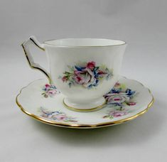 Gorgeous tea cup made by Aynsley in their crocus shape. Tea cup and saucer are white with large roses. Gold trimming on cup and saucer edges, as well as on angular handle. Excellent condition (see photos). Markings read: Est 1775 Aynsley England Fine English Bone China For more
