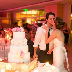 Jena and James share a kiss at the reception in the La Pacifica Ballroom after cutting into their wedding cake.