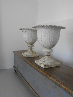 Pair of 19th century weathered iron urns with original white paint