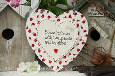 Handmade double heart sign with a red rose floral fabric background.  Plaque reads 'Bless this house with love, friends and laughter'.