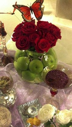 Flowers in vase filled with apples and water for haft seen