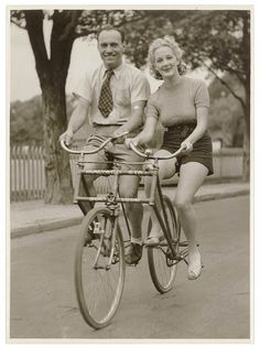 Man and woman on a Malvern Star abreast tandem bicycle, 1930s, by Sam Hood.