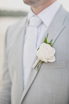 Simple design button hole for the groom to match up with bride's bouquet.