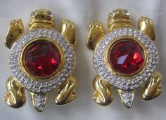 "These clipback earrings are slightly over 1 1/2"". They are rhinestone turtles with large red center glass stones. They are signed on back with the V logo for VALENTINO. Great looking earrings in excellent vintage condition.    