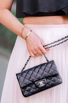 Schwarze Chanel Classic Tasche in Mini-Größe kombiniert mit einem pinken Tutu-Rock und Cartier Love Schmuck
