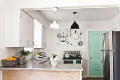 I love this kitchen, especially the pegboard and the color of the door! We could do some of this in our kitchen!