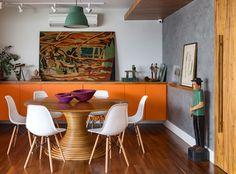 Decoração de apartamento, decoração com estilo, na sala de jantar com mesa redonda cadeiras brancas, armário laranja, laranja, obras de arte, quadro.