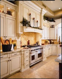kitchen cabinets, rope detail on uppers, lighting in niches, mantle on range hood. Rope corbels on lower cabs next to drawers.