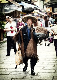 Years ago this man used his bird to catch fish. A string tied around the birds neck would prvent it from swallowing the fish. Shanghai, Beijing, We Are The World, People Around The World, Fishing World, Arab Men, Guilin, Chinese Style, Chinese Design