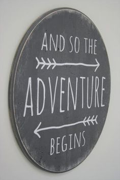 "And so the adventure begins! This is a wood sign that measures 20"" round. The background shown here is Dark Gray. Lettering is White.This piece is hand painted"
