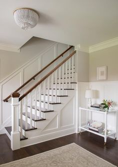 White and gray entry boasts upper walls painted soft gray and lower walls clad in board and batten trim lined with a white bamboo console table with mirrored shelves filled with s white triple gourd lamp next to a staircase illuminated by a white beaded flush mount, AERIN Jacqueline Flush Mount In Hand-Rubbed Antique Brass .
