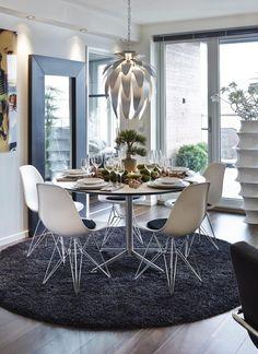 NATURLIGE INNSPILL: Interiørarkitekten toknatur inn i leiligheten i form av mose, treog gran. Det runde bordet er fra Ikea,og teppet fra Ege. Eames-stolene er fraVitra. De mørke gulvplankene Karelia EikStory Smokes Roastery Brown er 18,8 cmbrede, fra Parkettstudio. Den høye hvitevasen er fra Roggens.