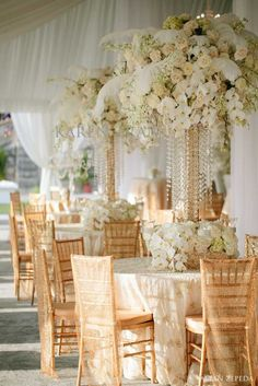 A Great Gatsby wedding theme - gold candelabra's  and white feathers with a soft pallet of floral.