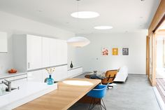 A handful of modernist classics—an Eames Lounge, a Bubble Lamp by George Nelson, and a shell armchair from Modernica—kit out the living room and kitchen in the Shozi Residence. Photo by: Jessica Haye + Clark Hsiao   Read more: http://www.dwell.com/articles/Looking-Inward.html