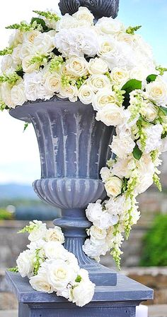 A large gray urn is filled with a cascade of white roses, hydrangeas and freesia.
