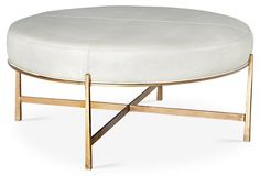 In a sleek limestone leather and gleaming gold frame, our Rho cocktail ottoman is the perfect place to take a seat at your next party.