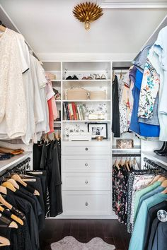 Chic walk-in closet features white built-ins, with backs of shelves lined with black and white wallpaper, illuminated by a Candelabra Home Broche Collection Flushmount Antique Gold.