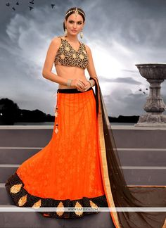 Alluring orange net designer lehenga choli with embroidery, resham, zari, lace and patch border work. As shown matching velvet choli and dupatta comes with this.(Slight variation in actual color is po...