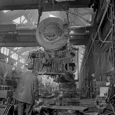 Title:Topeka, Kansas. Lifting an engine with the eighty-ton cranes at the Atchison, Topeka, and Santa Fe Railroad locomotive shops. This locomotive will be carried to another part of the shop…