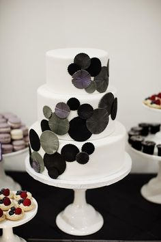 modern wedding cake decorated with cascading round disks in shades or gray and purple | photo: Photogen Inc